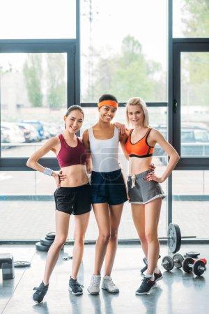happy multiethnic sportswomen standing together at gym
