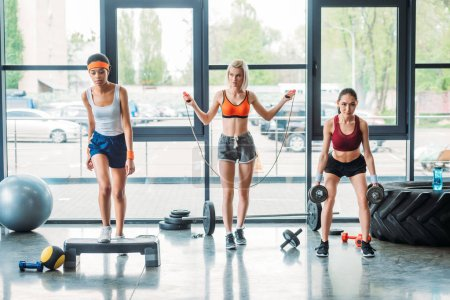 african american sportswoman exercising on step platform, caucasian female athlete doing jump rope workout and asian sportswoman doing exercise with dumbbells at gym