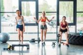 african american sportswoman exercising on step platform, caucasian female athlete doing jump rope workout and asian sportswoman doing exercise with dumbbells at gym