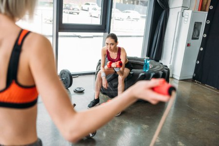 cropped image of sportswoman doing jump rope workout while asian femae athlete sitting on training tire with bottle of water and exercising with dumbbell at gym