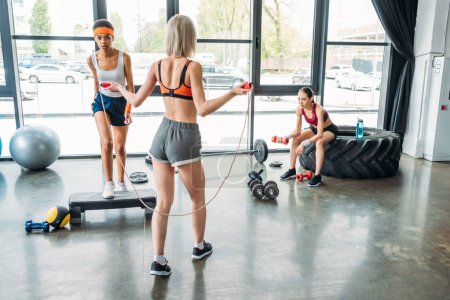 rear view of sportswoman doing exercise with jump rope, african american female athlete exercising on step platform and asian sportswoman doing exercise with dumbbell at gym