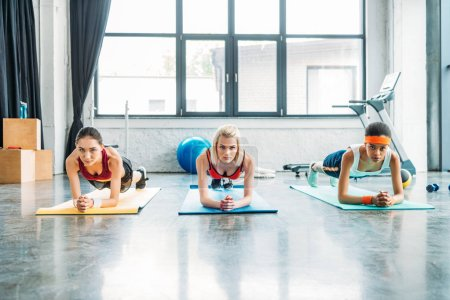 Photo for Front view of multiethnic female athletes doing plank on fitness mats at gym - Royalty Free Image