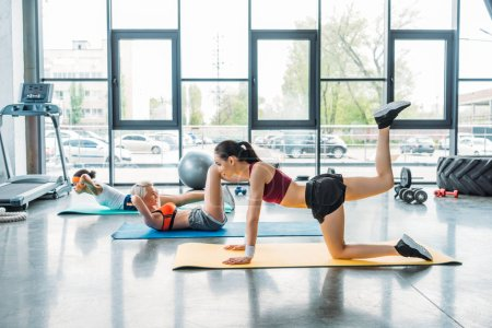 side view of three multiethnic female athletes exercising on fitness mats at gym