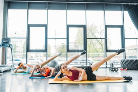 young multicultural sportswomen doing aerobics exercise on fitness mats at gym