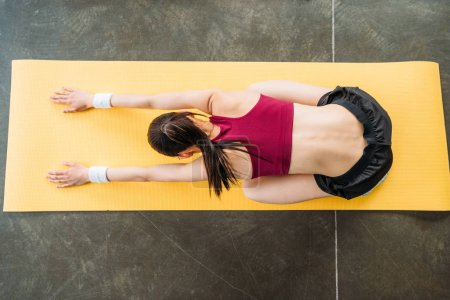 Photo for High angle view of sportswoman stretching on fitness mat at gym - Royalty Free Image