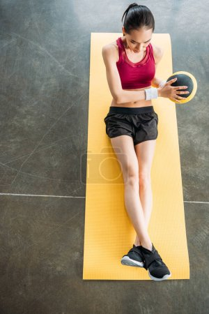 Photo for Elevated view of asian sportswoman exercising with ball on fitness mat at gym - Royalty Free Image