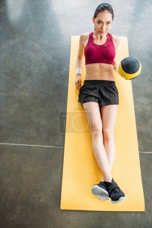 young asian sportswoman with ball on fitness mat at gym