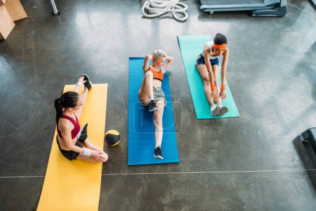 high angle view of three multiethnic sportswomen exercising on fitness mats at gym