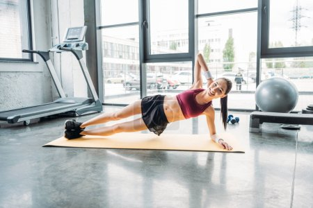 smiling asian sportswoman doing side plank on fitness mat at gym