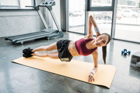 young smiling female athlete doing side plank on fitness mat at gym