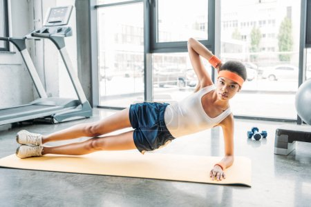 african american sportswoman doing side plank of fitness mat at gym