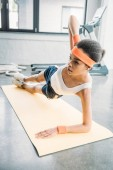 young african american sportswoman in headband and wristbands doing side plank on fitness mat at gym