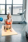 young female athlete exercising on fitness mat at gym