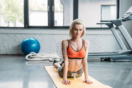 smiling young sportswoman exercising on fitness mat at gym