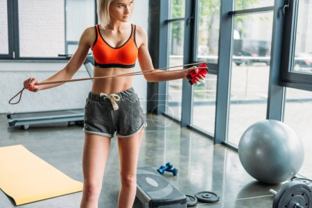 sportswoman standing and holding jump rope at gym