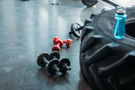 different dumbbells, abs roller and bottle of water on training tire at gym