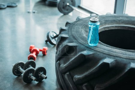 closeup view of different dumbbells, abs roller and bottle of water on training tire at gym
