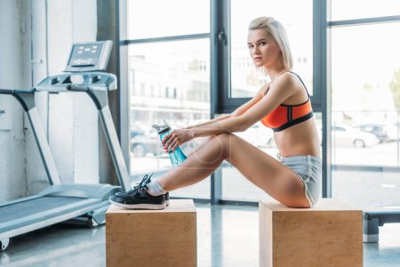 attractive sportswoman sitting on wooden box with bottle of water in front of treadmill at gym