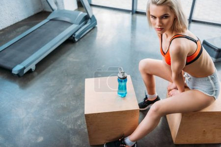high angle view of young attractive sportswoman resting on wooden box after work out at gym