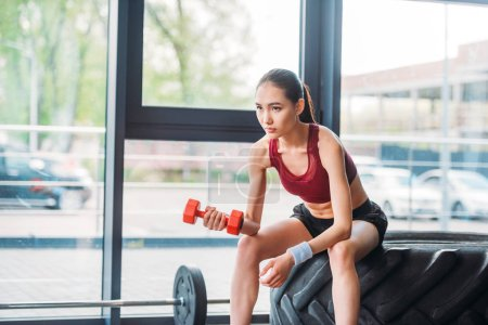 asian female athlete with dumbbell sitting on training tire at gym