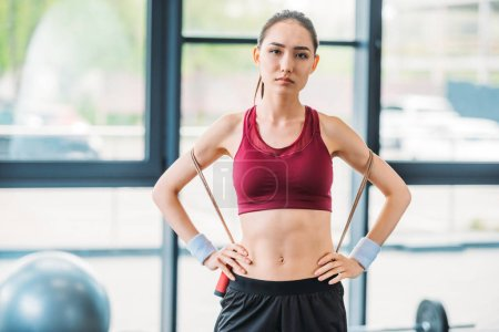 portrait of young asian sportswoman with skipping rope looking at camera at gym