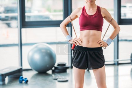 partial view of sportswoman with skipping rope standing akimbo at gym