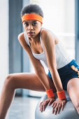 portrait of young african american sportswoman sitting on fitness ball at gym