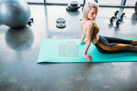side view of young athletic woman resting on fitness mat after work out at gym