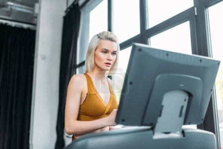 portrait of young sportswoman running on treadmill at gym