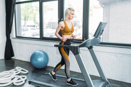 side view of young sportswoman running on treadmill at gym