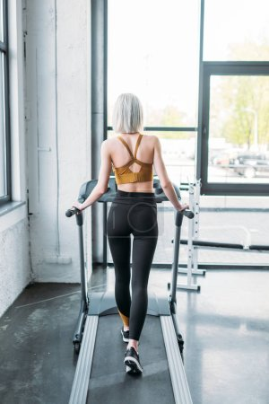 Photo for Back view of sportswoman training on treadmill at gym - Royalty Free Image