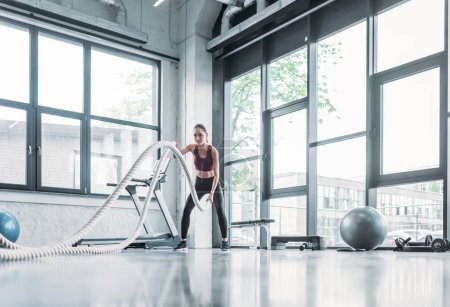 Photo for Asian sportswoman working out with battle ropes at gym - Royalty Free Image