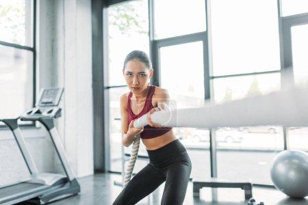 young asian sportswoman working out with battle rope at gym