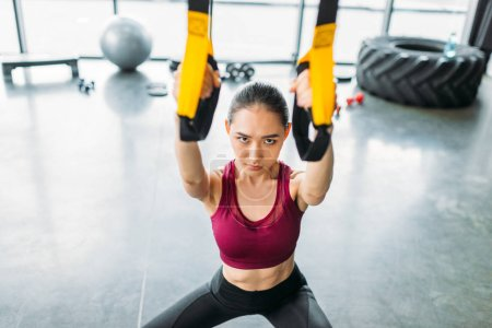 high angle view of asian female athlete training with resistance bands at gym