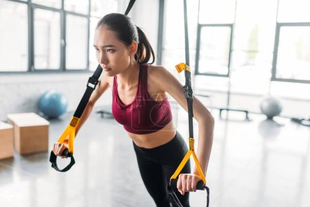 asian female athlete training with resistance bands at gym