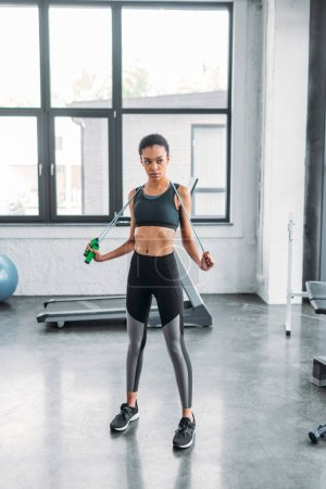 young african american sportswoman with jumping rope standing at gym