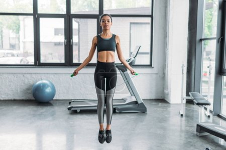young african american sportswoman exercising with jumping rope at gym