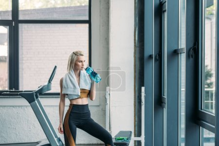 young sportswoman with towel drinking water from sportive water bottle after workout at gym