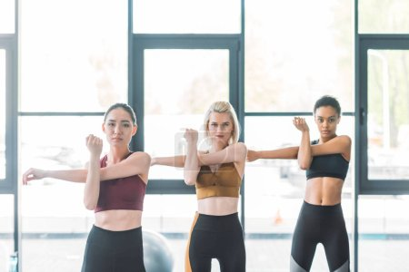 portrait of attractive multiracial sportswomen stretching before working out at gym