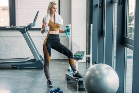 young sportswoman with sportive water bottle and towel standing on step after workout at gym