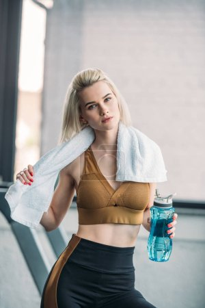 portrait of young sportswoman with sportive water bottle and towel after workout at gym