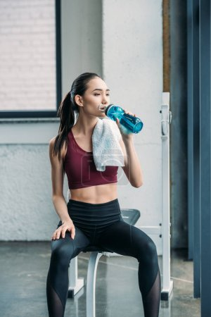 Photo for Asian sportswoman with towel drinking water from sportive water bottle after workout at gym - Royalty Free Image