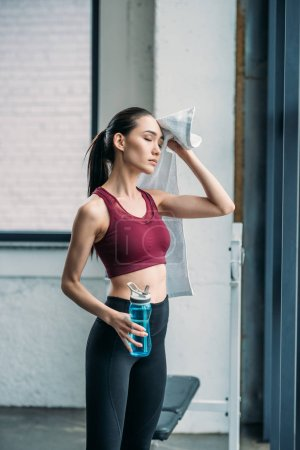 Photo for Tired asian sportswoman with towel and water bottle after workout at gym - Royalty Free Image