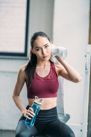 tired asian sportswoman with towel and water bottle after workout at gym