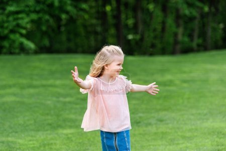 cute happy little child with open arms looking away in park