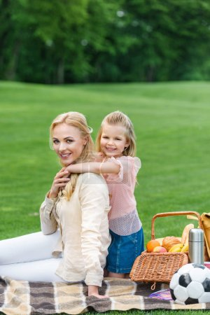 happy mother and daughter hugging and smiling at camera while sitting together on plaid at picnic