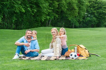 happy family smiling at camera while sitting together on plaid at picnic