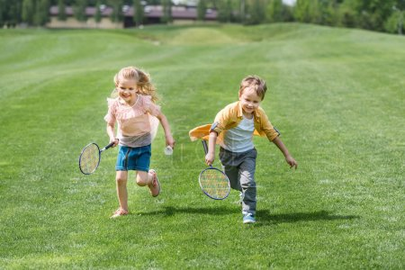 cute smiling children with badminton rackets running together in park