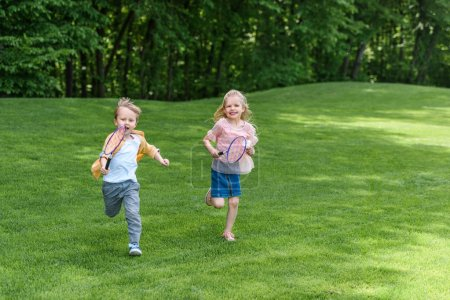 Photo for Adorable smiling children with badminton rackets running together in park - Royalty Free Image