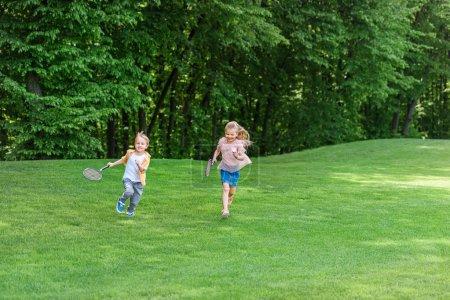 Photo pour Mignon petit enfants avec des raquettes de badminton, exécutant ensemble dans le parc - image libre de droit